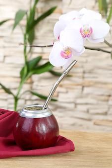 Чайный помощник в калебасе и орхидее на фоне каменной стены