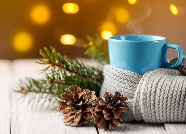 Чайная кружка накрыта тёплым вязанным шарфом с шишкой и еловой веткой. уютный фон атмосферы рождества.