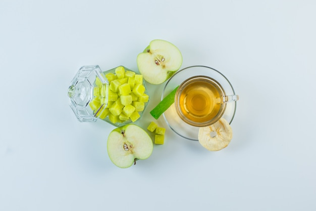 Tea in a mug with apple, dried fruit, sugar cubes, candy flat lay on a white background
