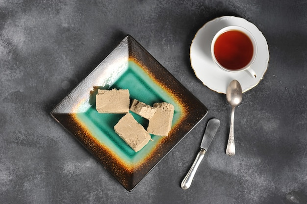 Tea in a mug with a golden edge and a saucer and halva cut into pieces