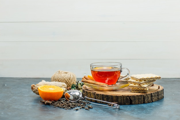 Tea in a mug with herbs, orange, spices, waffle, thread, wooden board, strainer side view on white and stucco background