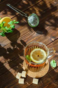 Tea in a mug with leaves, lemon and sugar cubes