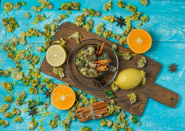 Tea in a mug with spices, orange, lemon, dried herbs top view on blue and cutting board
