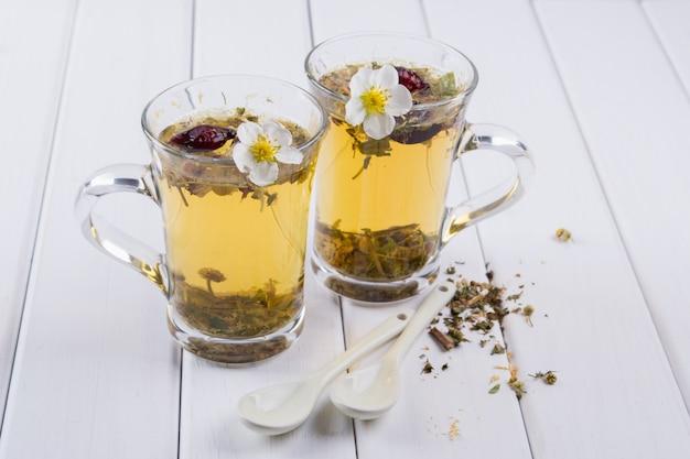有用なハーブと花のお茶。 2つのガラスのコップ。お茶の材料