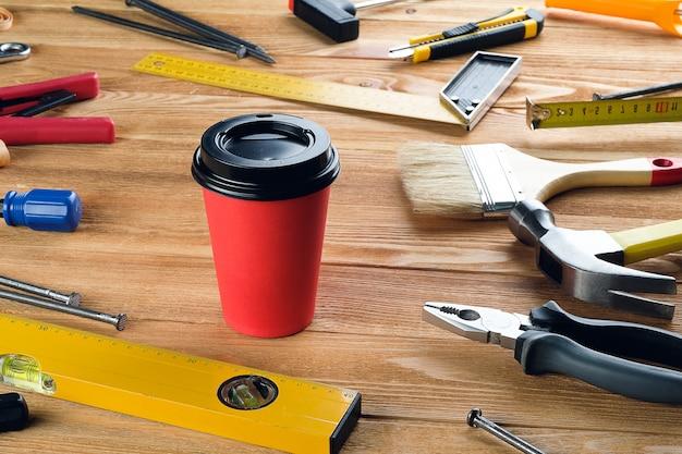 使い捨てカップのお茶またはコーヒー、木製のテーブルの専門家の建設または家の修理のためのツール
