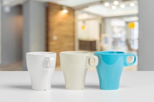 背景をぼかした写真のテーブルにお茶やコーヒーのマグカップ