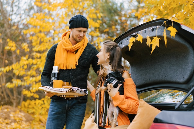 Tea party in car trunk - loving couple drinks hot tea from thermos flask sitting in trunk