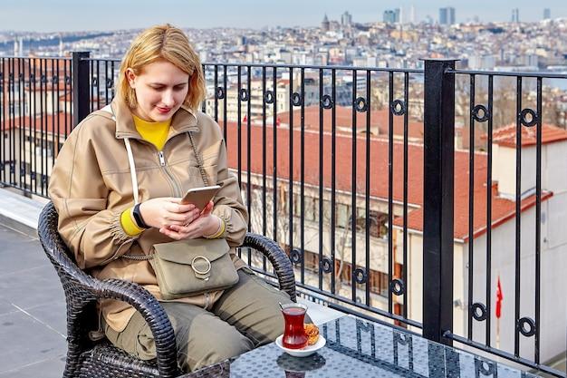 이스탄불 도시가 내려다 보이는 호텔 옥상의 티 파티. 뜨거운 음료가 식 으면서 젊은 여성이 온라인 메시지를 스캔합니다.