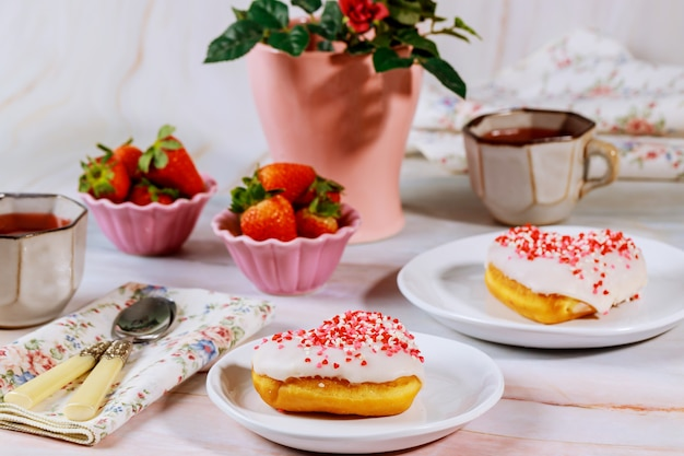 Tea party table with heart shaped donuts, strawberry and rose.