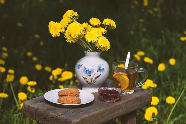 花の背景の庭でクッキーとジャムのティーパーティー。田舎風の食べ物の静物