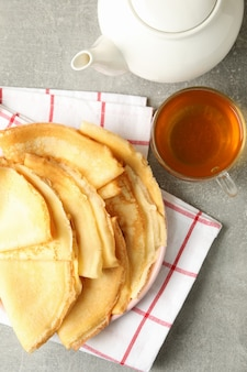 Tea, and plate of thin pancakes on gray table