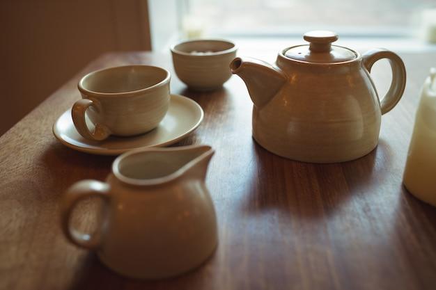 나무 테이블에 차 주전자와 커피 컵