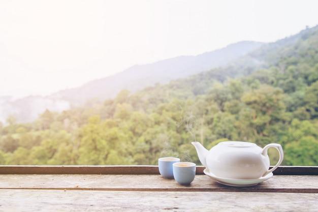 나무 테이블에 뜨겁거나 따뜻한 차 주전자와 차 잔