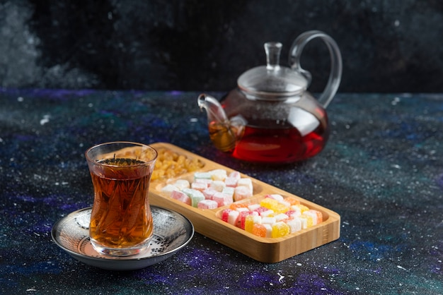 Tea pot and glass of tea with delights
