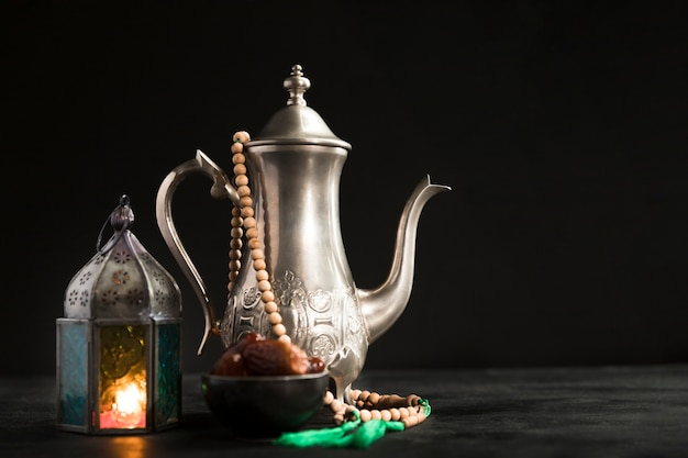 Tea pot with candle beside prepared for ramadan day