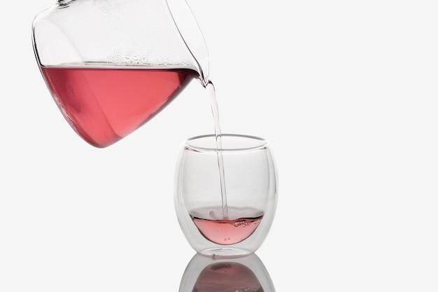 Чай наливается в стеклянную чашку с двойными стенками, изолированную в белом