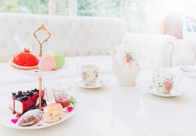 白い大理石のテーブルに置かれたお茶セットとケーキ