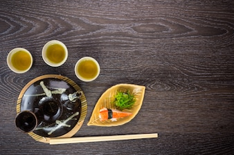 Tea set and sushi on wooden table