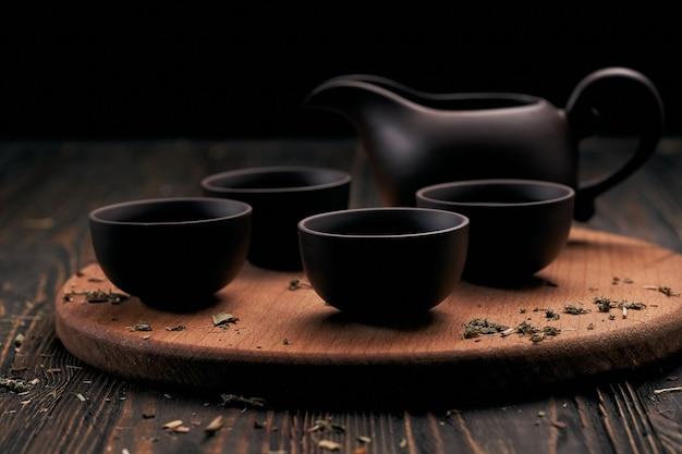 Чайный сервиз и чайные листья на деревянной кухонной доске