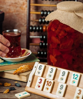 A tea set around a game, domino table with a big jar of confiture.