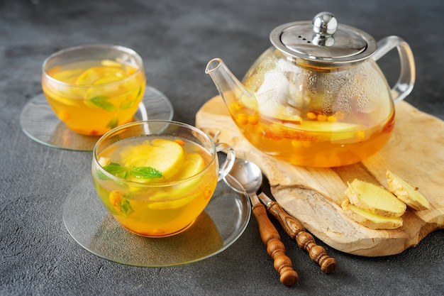 Tea set composition with hot tea on dark grey surface