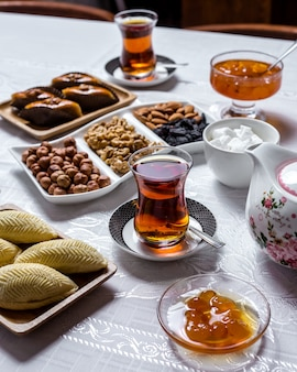 Tea set shakarbura white cherry jam nuts dry fruits tea in armudy side view