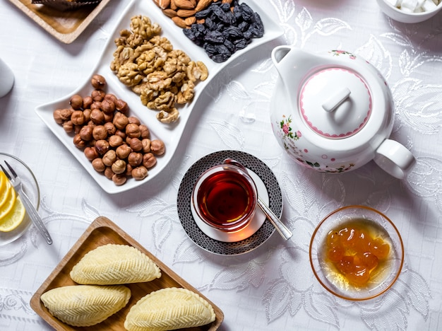 Tea set shakarbura white cherry jam nuts dry fruits tea in armudy top view