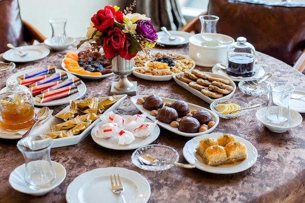 Tea set with candies, dried fruits and nuts, cookies, jams, lemon and baklava