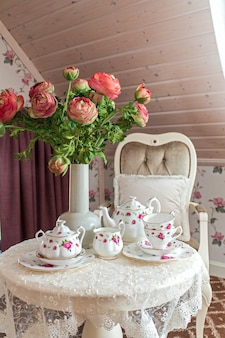 Tea set with flowers on the table in the morning