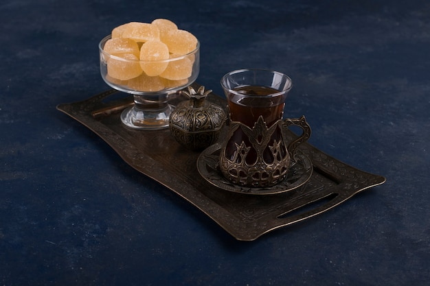 Tea set with a glass of tea and marmelades on a metallic platter