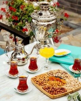 Чайный сервиз со сладостями и черным чаем в бокале armudu