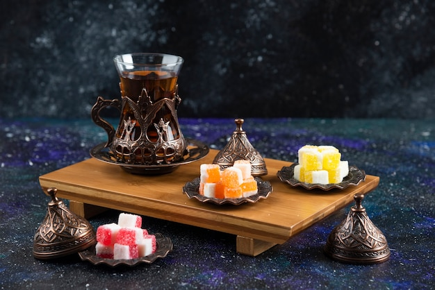 Tea set with turkish delights on wooden board