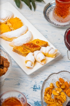 Tea set with varieties of traditional nuts, lemon, confiture and sweets served on white tablecloth