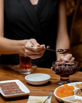 Tea setup with strawberry jam, black tea, chocolate bar, dried fruits