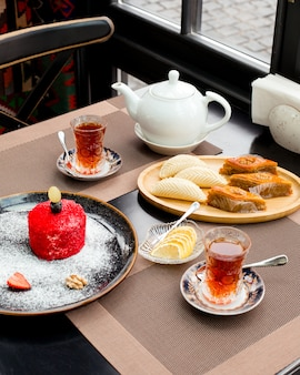 A tea setup with tea in pear-shaped glass plates of red velvet cake pakhlava and shakarbura