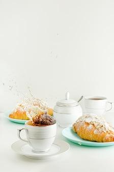 カップにお茶のスプラッシュ。焼きたてのクロワッサンと白い朝食タベ。