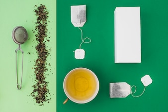 Tea strainer, tea bag and white boxes on green background