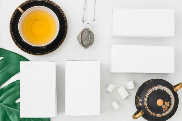 Tea strainer and white boxes with sugar cubes on white background