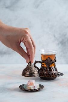 Tavolo da tè. uomo che apre le stoviglie della caramella accanto al tè