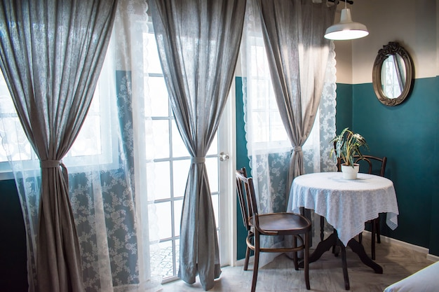 Чайный столик с горшками для растений рядом с большими окнами и большими серыми шторами с солнечным фильтром.