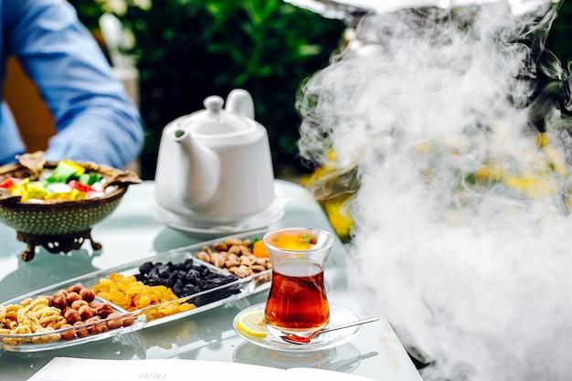 Чайный столик из конфет, орехов, белого чайника и пара.