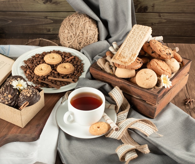 Tea table with pralines, cookies and a cup of tea