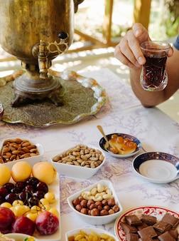 Чайный столик с самоваром, фруктами, шоколадом, орехами и сладостями.