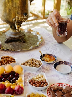 Tea table with samovar, fruits,chocolate, nuts and sweets.