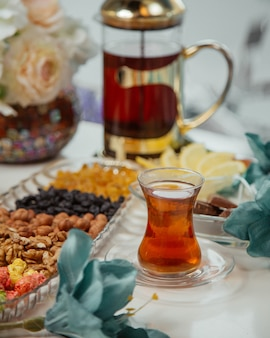 Tea table with sweets and nuts and a glass of tea.