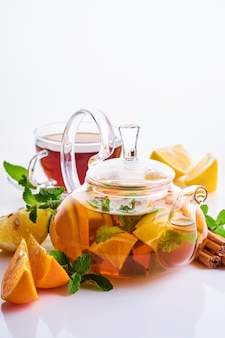 Tea in a teapot with slices of lemon, orange, mint and cinnamon sticks isolated on a white table.