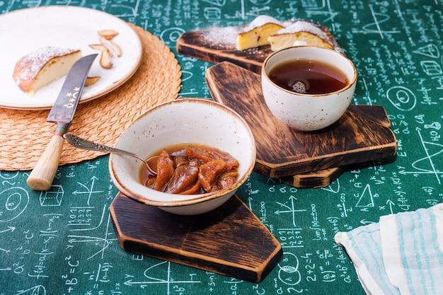 ティータイム、アプリコットジャム、カッテージチーズのパイ、木の板にお茶、テーブルクロスの背景に数式。