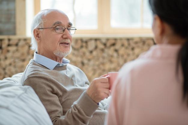 Время чая. привлекательный приятный старший мужчина разговаривает, позирует на размытом фоне и наслаждается жизнью