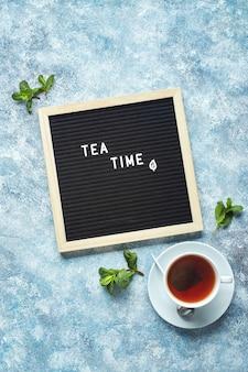 ミントの葉とお茶のガラスカップと青いテーブルにテキストとティータイム黒文字ボード
