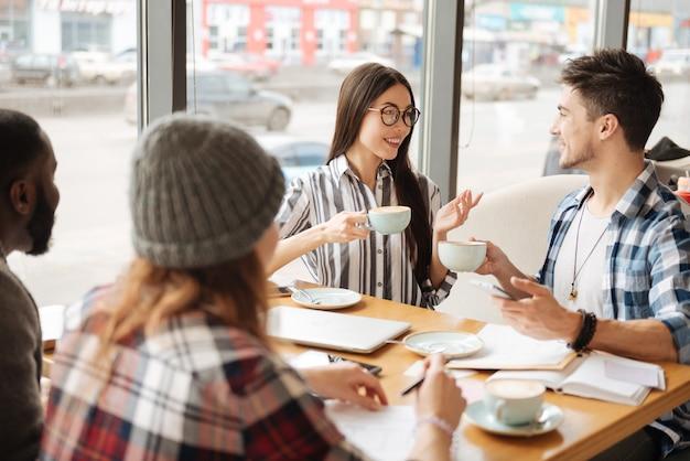 차 시간. 친구와 카페에서 차를 마시는 동안 그녀의 남자 친구와 좋은 대화를 나누는 행복 한 미소 아시아 여자.